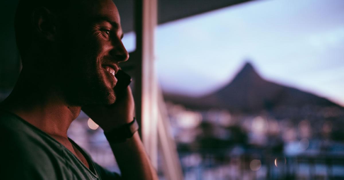 Smiling man talking on mobile phone