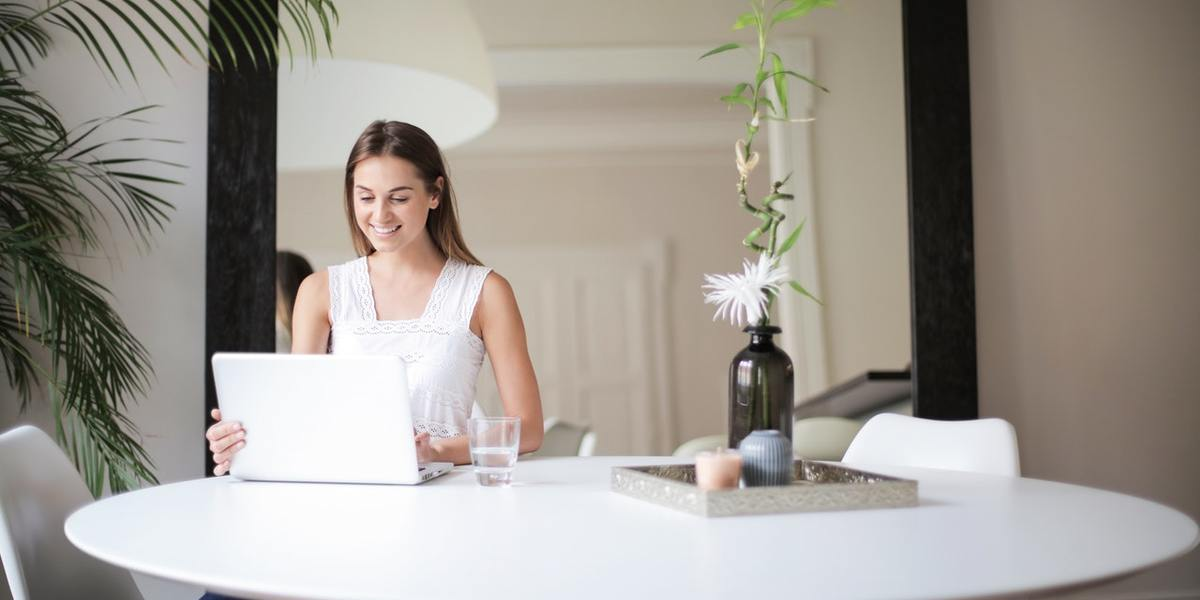 smiling young woman with laptop at table