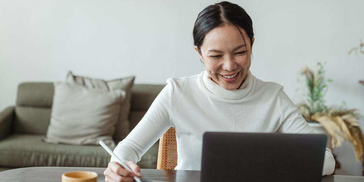 woman working on laptop and making notes on checklist