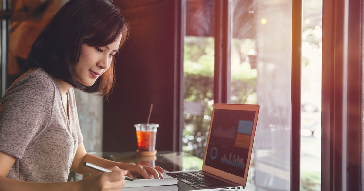 A woman freelancer working on project with laptop and writing notebook in a cafe