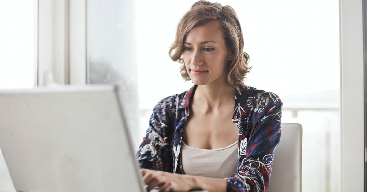 Woman writing on laptop at desk