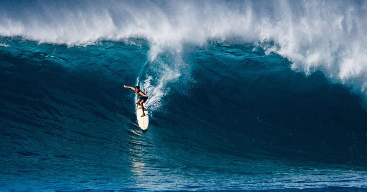A surfer takes on Waimea Bay, Hawai'i