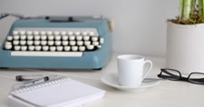 Typewriter, notepad, pen, cup and saucer, eyeglasses, and plant on a desk