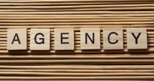Wooden letter tiles spelling out the word Agency