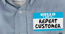 Close-up of name tag displaying Hello I Am a Repeat Customer